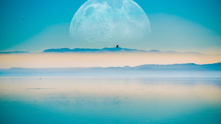 Large Moon on the Horizontal, Mountains and the Calm Sea.