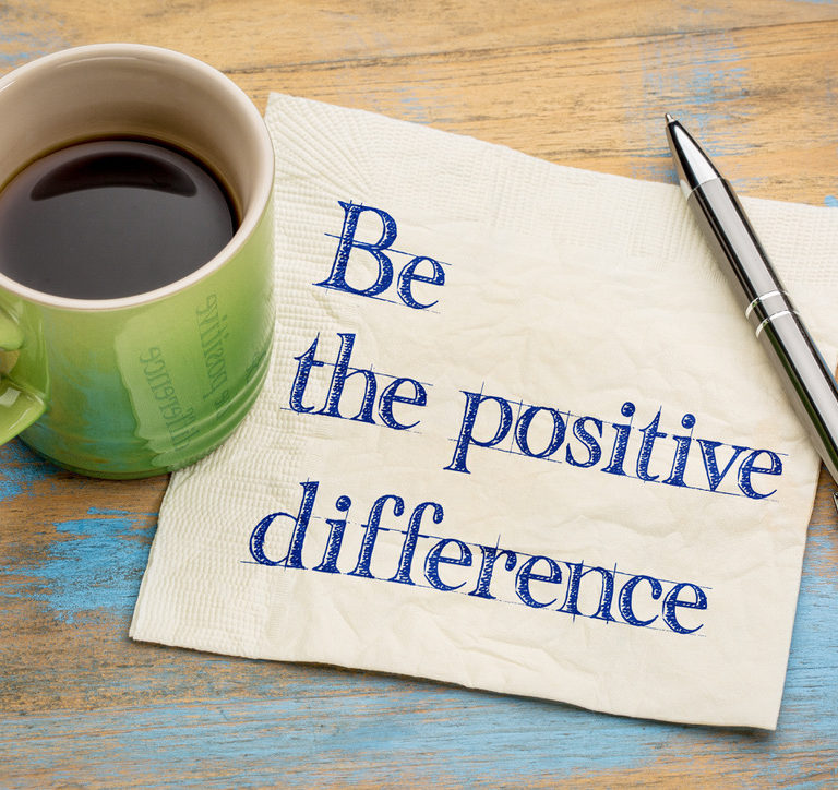 Coffee cup next to napkin with the message, be the positive difference