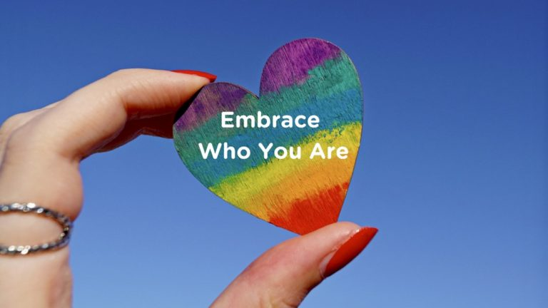 """Woman's hand holding a Pride heart that says, """"Embrace Who You Are"""""""