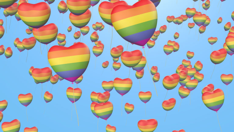 Gay Pride heart shaped balloons floating in the sky
